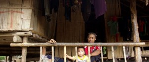 Family sit in front of their home at Mae La refugee camp